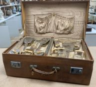 A 1930's Art Deco leather travelling toilet case, containing eleven silver mounted jars, mirror, and