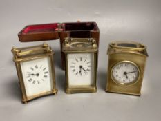 Three small gilt brass carriage timepieces, one with leather outer case, largest 10.5cm high