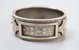 A late 19th century white and two colour yellow metal overlaid hinged bangle, gross 35.4 grams,