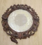 A Black Forest walnut wall mirror carved with roses, diameter 56cm