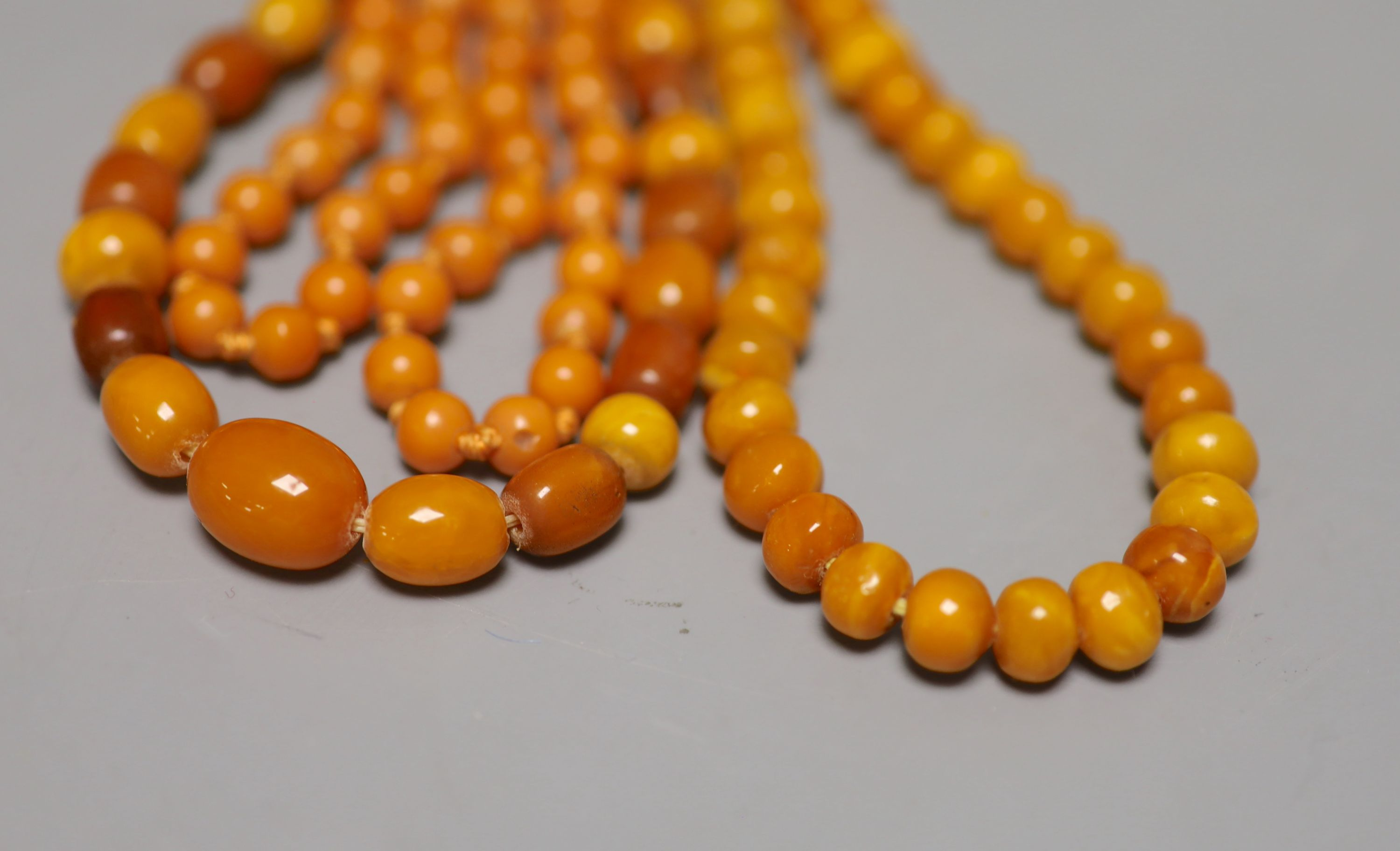 Two single strand amber bead necklaces, 106cm and 88cm, gross 95 grams and a reconstituted amber?
