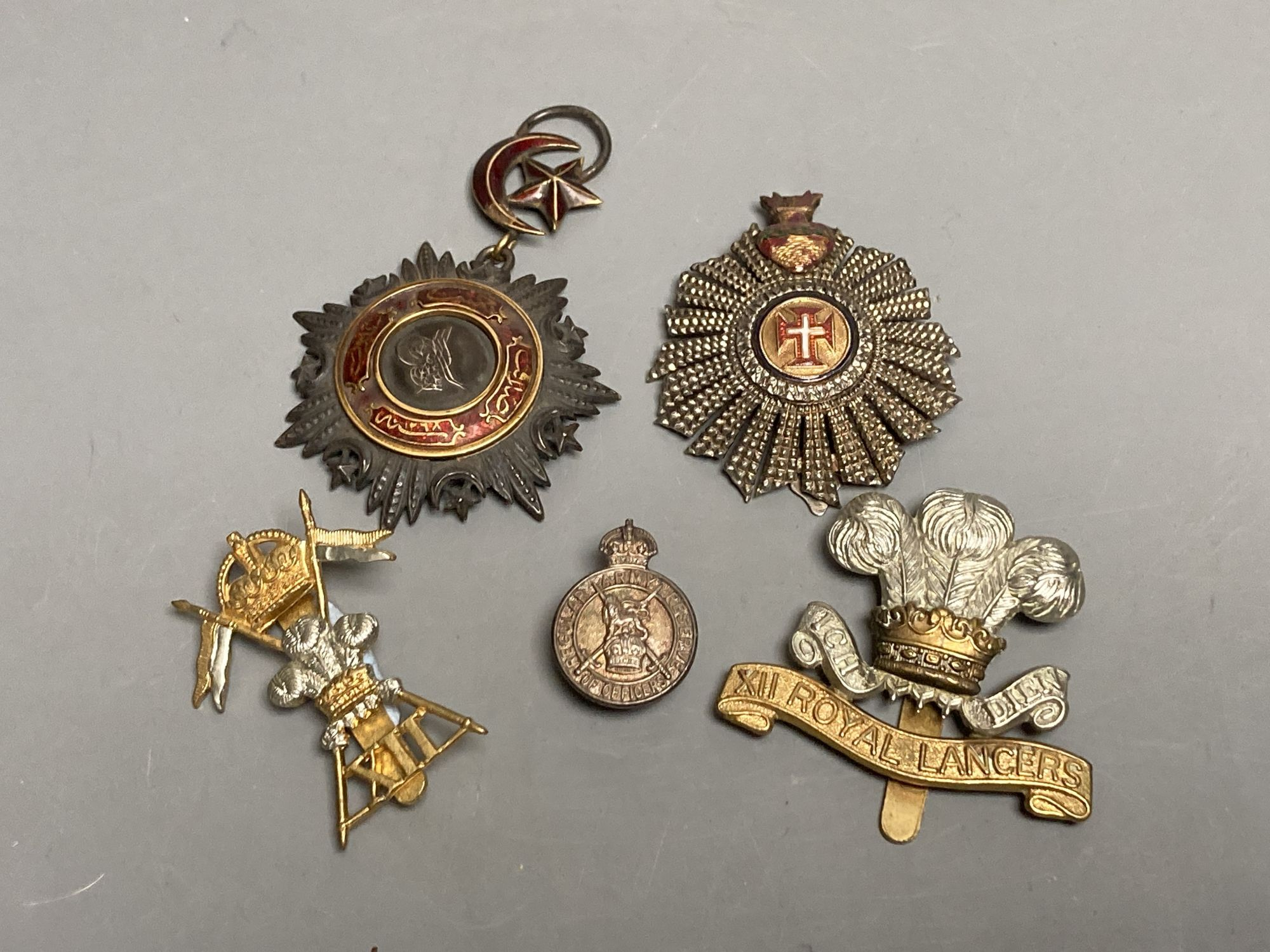 A Turkish Ottoman Order Medjidie Knights Star, another star and three English regimental badges