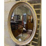 An oval gilt framed bevelled wall mirror, width 58cm height 78cm