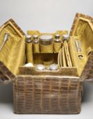 A late Victorian crocodile skin travelling toilet case containing seven silver mounted toilet