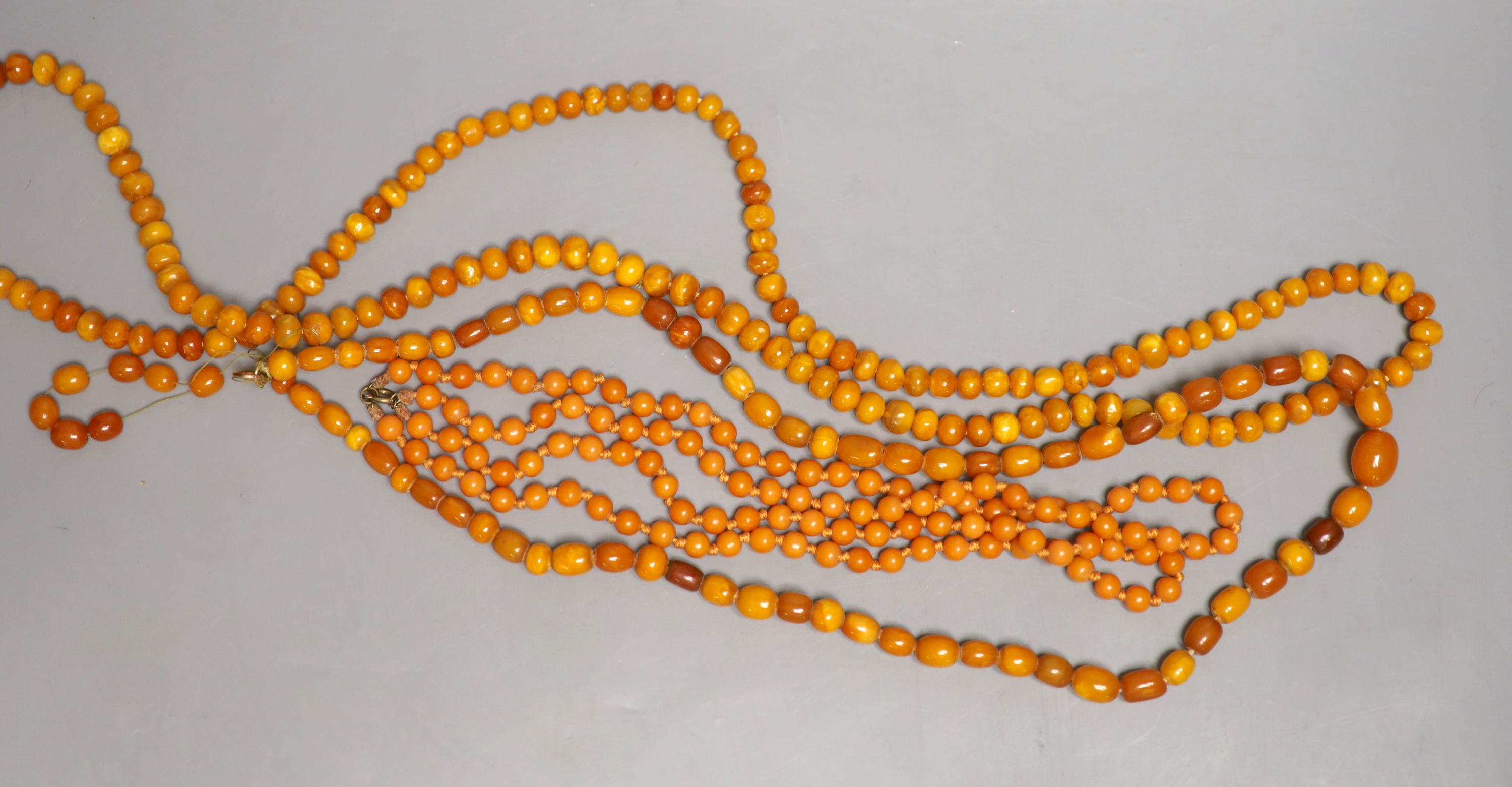 Two single strand amber bead necklaces, 106cm and 88cm, gross 95 grams and a reconstituted amber? - Image 2 of 2