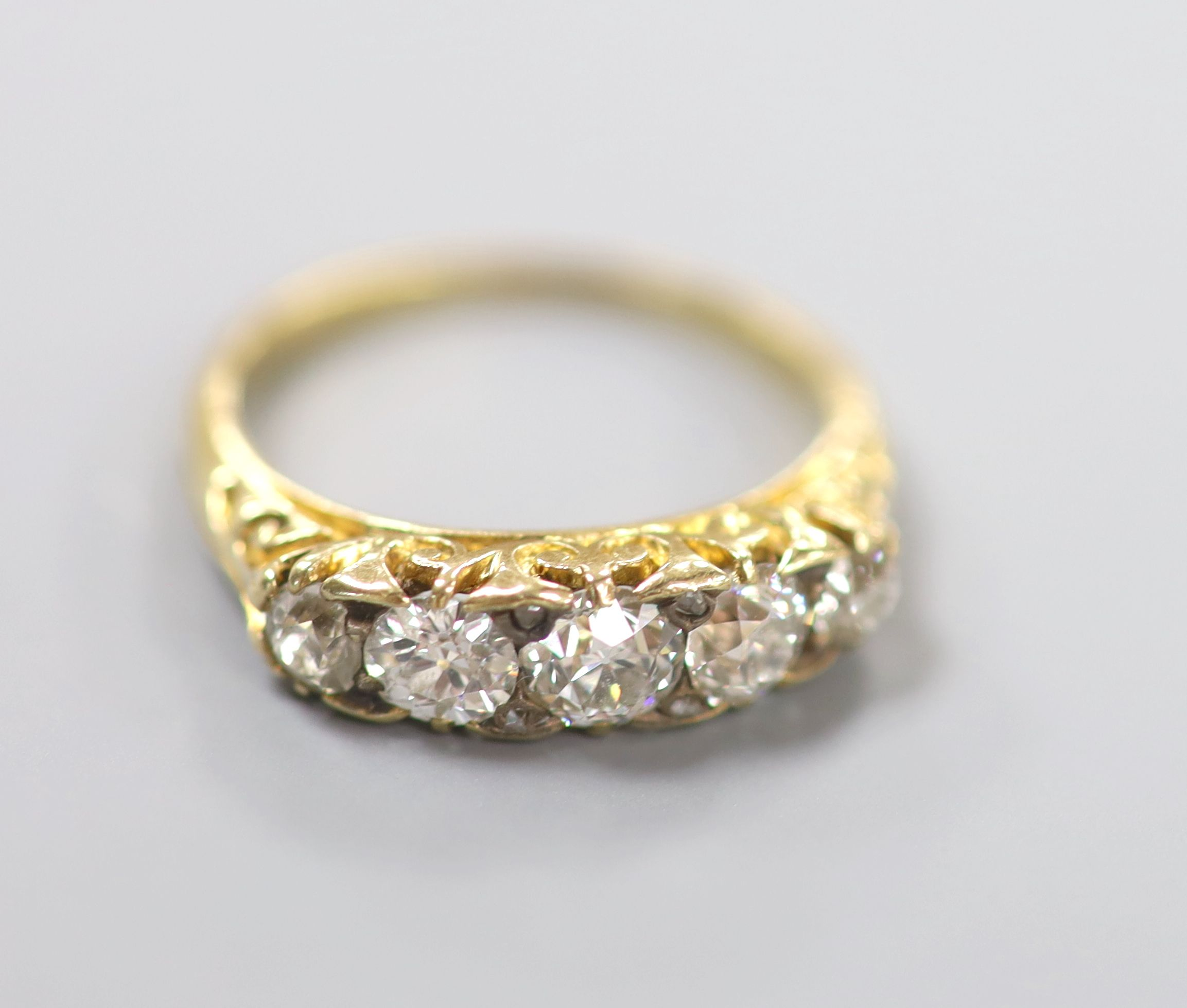 An early 20th century yellow metal and graduated five stone diamond set half hoop ring, size N,