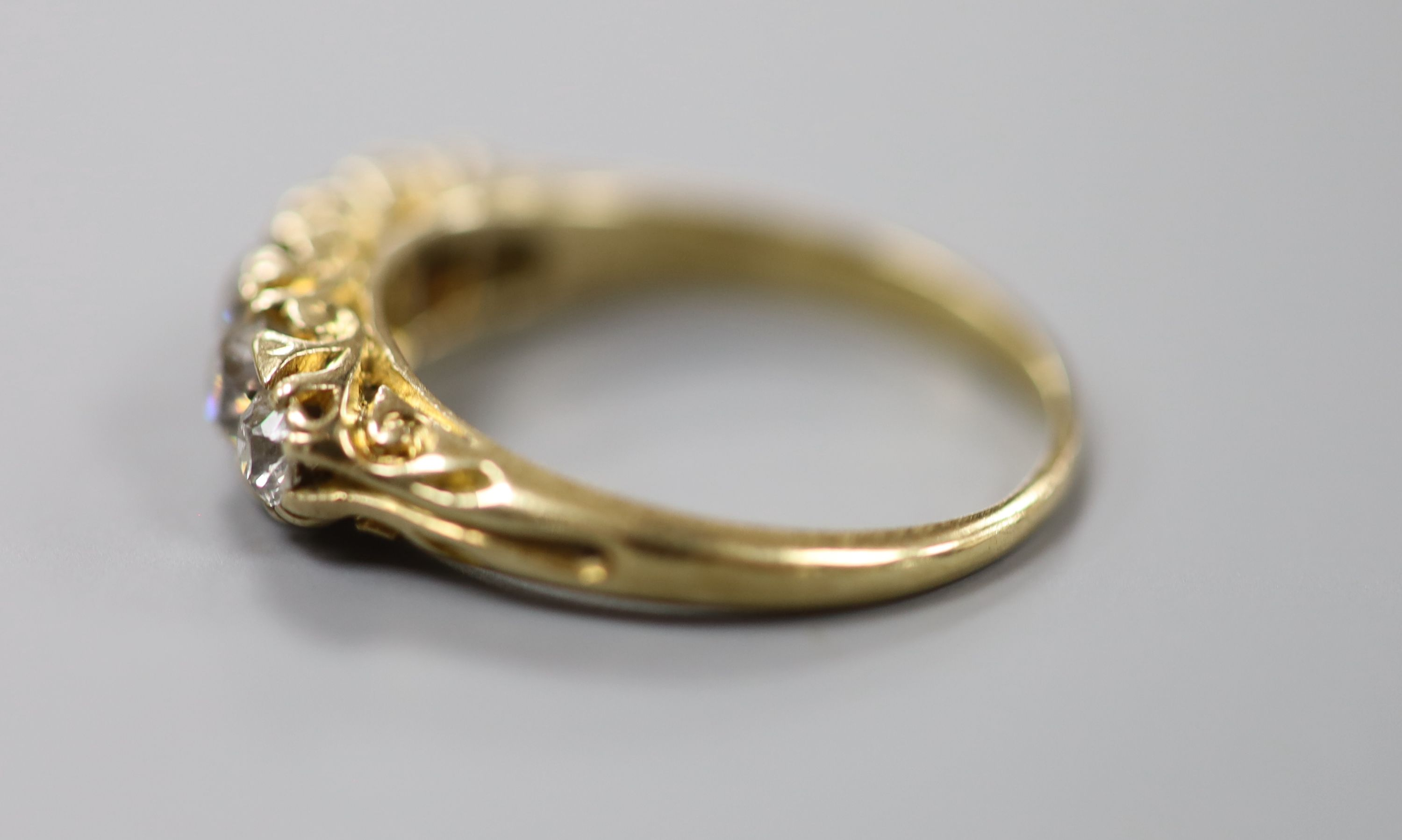 An early 20th century yellow metal and graduated five stone diamond set half hoop ring, size N, - Image 3 of 4