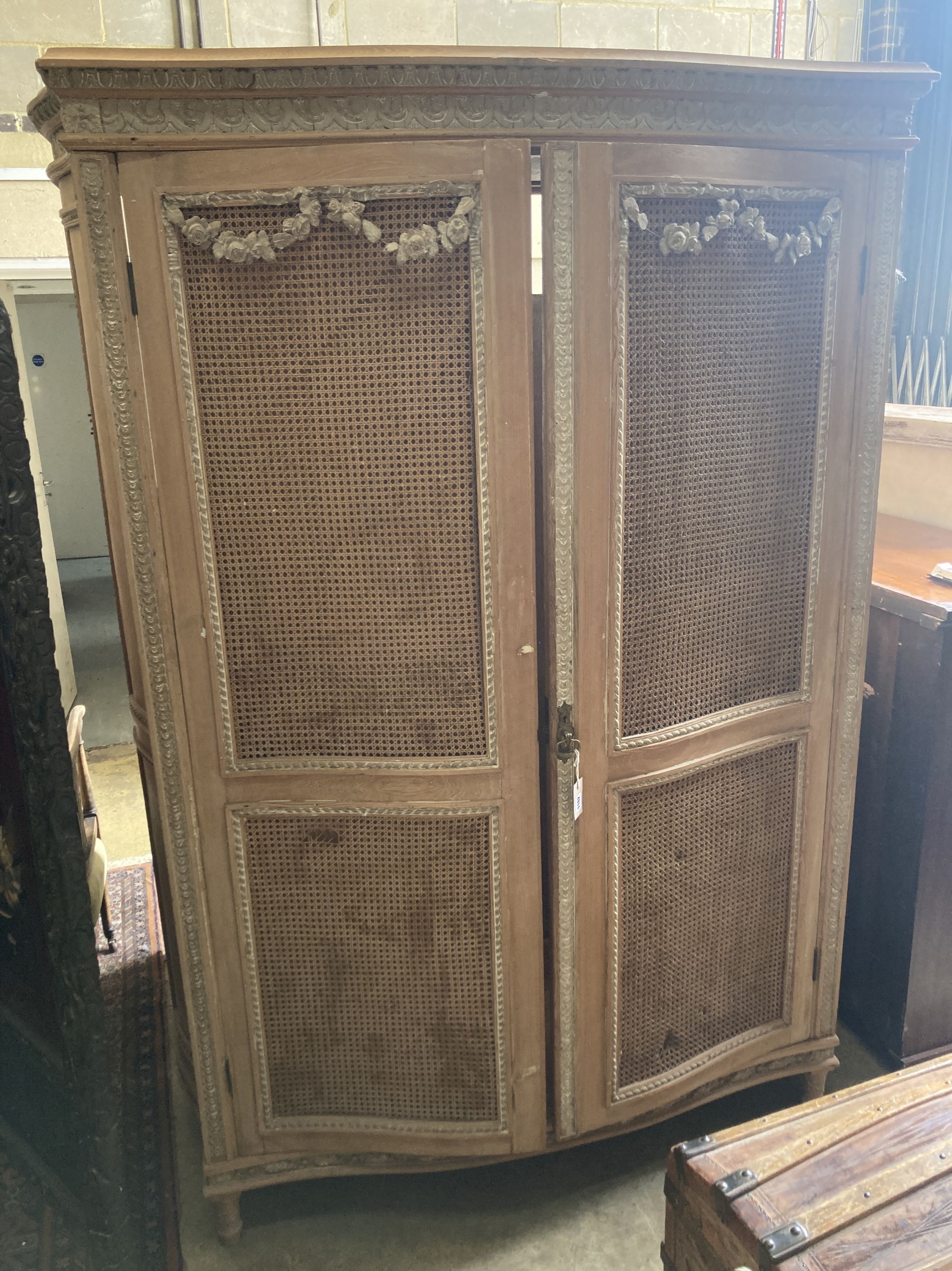 A French serpentine front caned pine armoire, width 154cm depth 60cm height 216cm