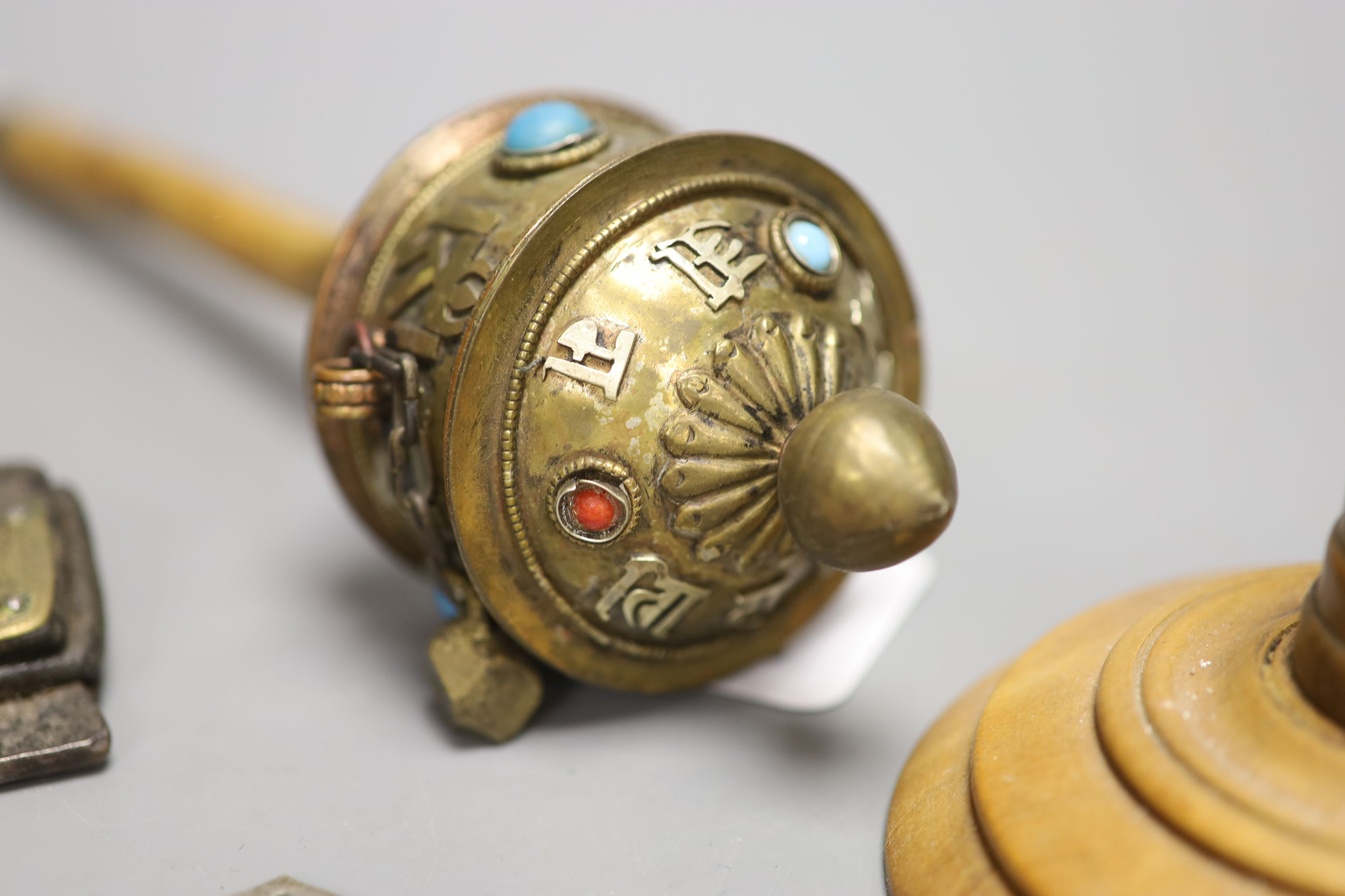 A Tibetan brass prayer wheel, inset with cabochons, with turned wood handle and four other items, - Image 3 of 4