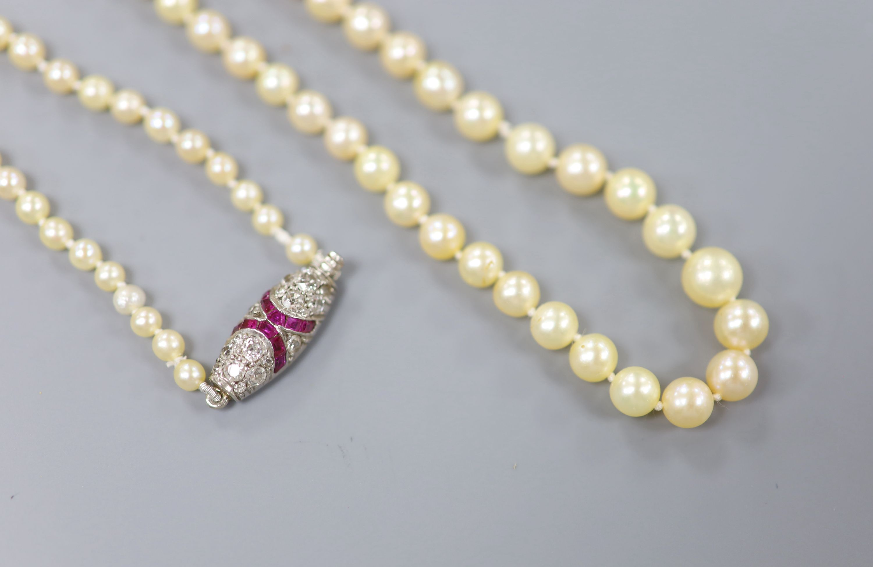 An early 20th century single strand graduated seed pearl necklace, with white metal ruby and diamond