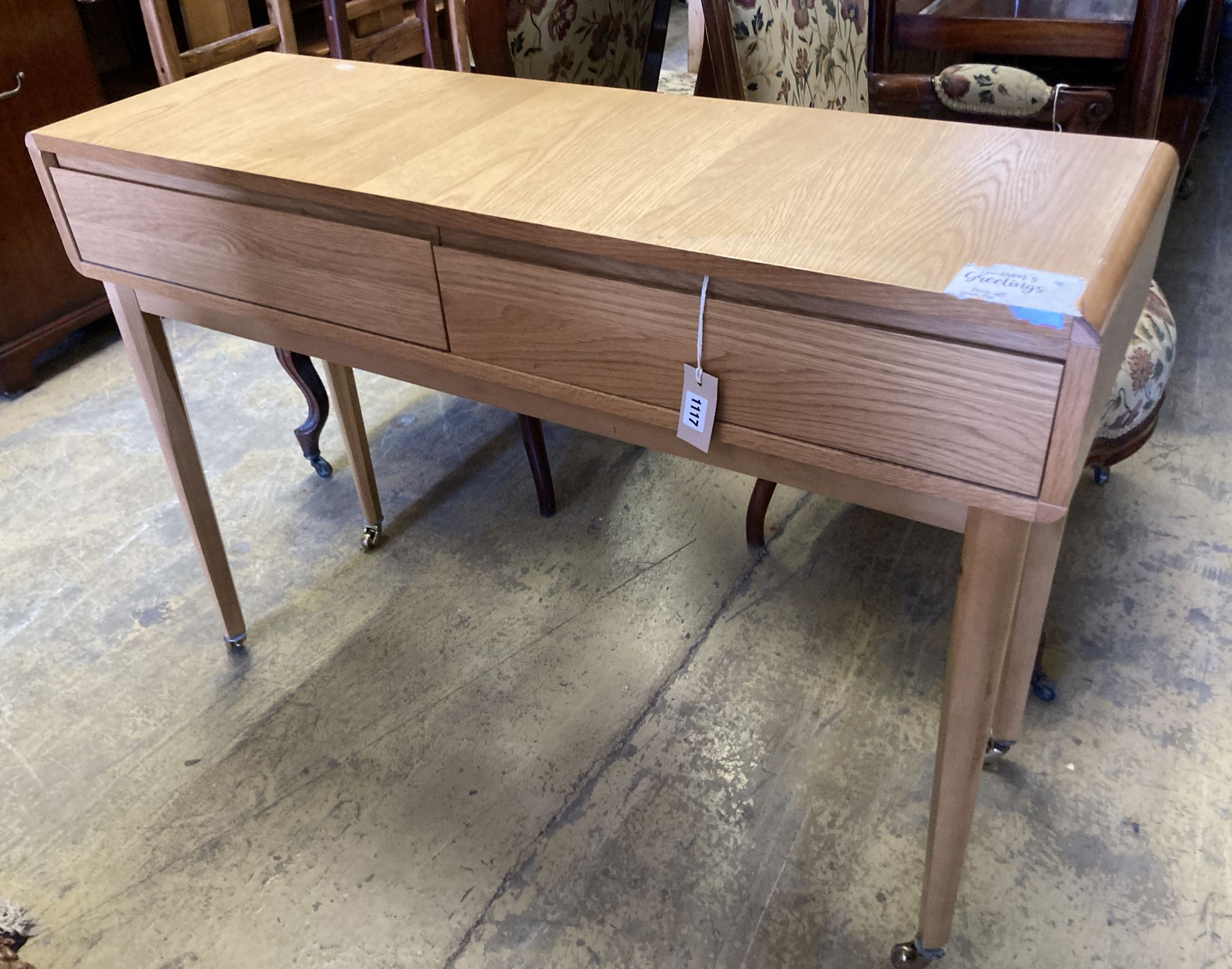 A contemporary oak two drawer side table, width 110cm, depth 35cm, height 79cm