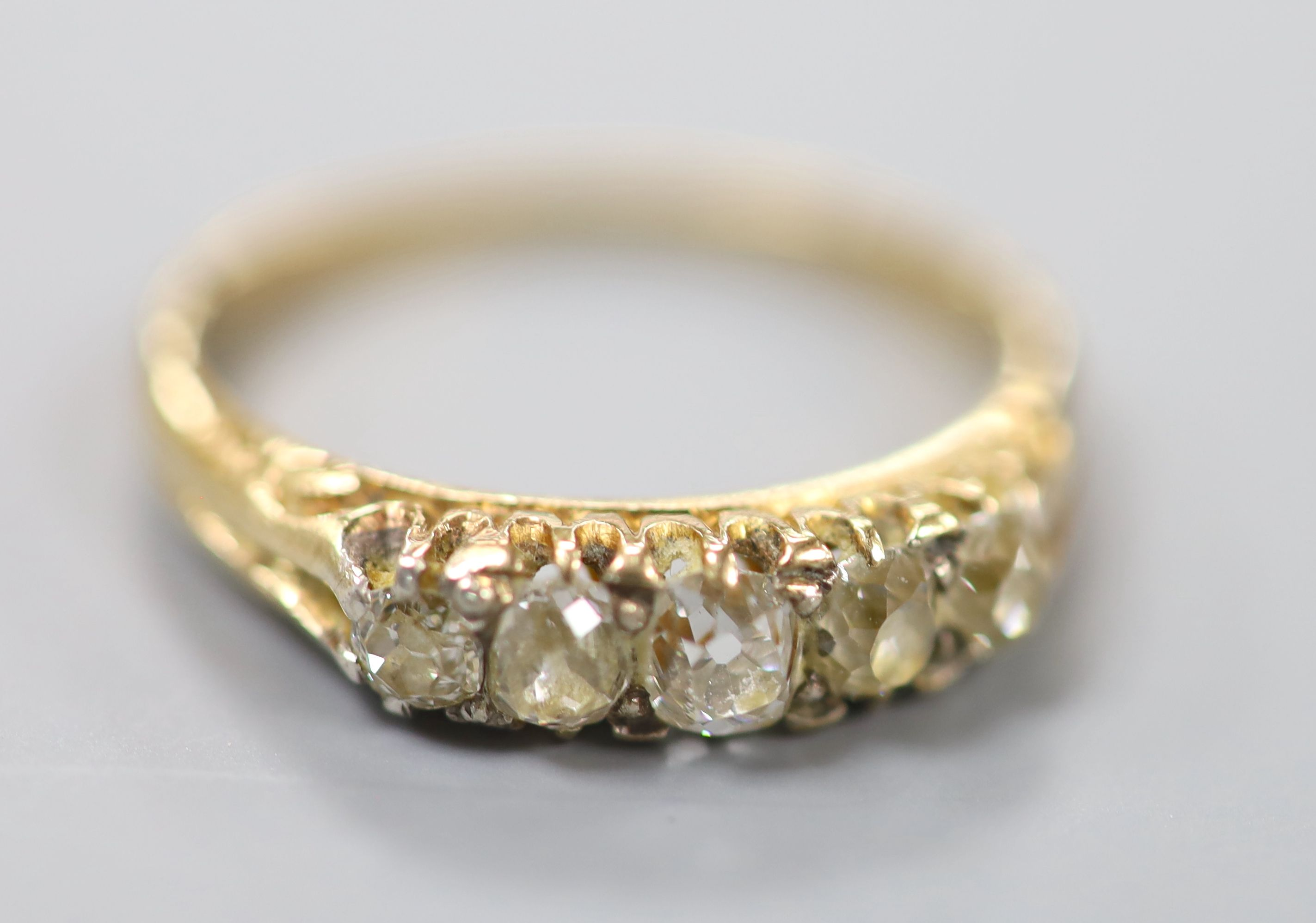 An early 20th century yellow metal and graduated five stone diamond set ring, size O, gross 2.6