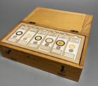 A collection of 48 histology slides contained in a fitted lightwood case, mainly botanical
