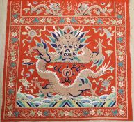 A early 20th century Chinese red felt square panel embroidered with a central motif of a dragon,