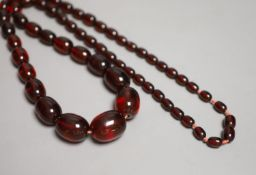 A single strand graduated oval simulated cherry amber bead necklace, 84cm, gross 90 grams.
