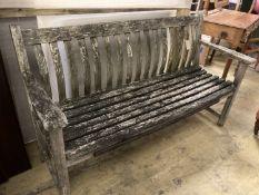 A weathered teak garden bench, length 150cm, depth 55cm, height 86cm