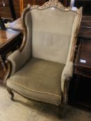 An early 20th century French parcel gilt carved beech wing armchair, width 70cm, depth 66cm,