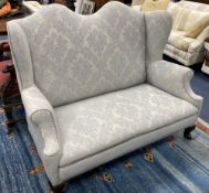 An early 20th century Queen Anne style upholstered wing back settee, length 140cm, depth 75cm,