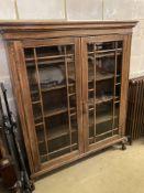A 1920's glazed oak two door bookcase, length 130cm, depth 29cm, height 156cm
