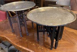 Two Benares engraved circular tray top tables, larger 59cm diameter, 53cm high