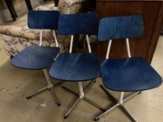A set of three mid century stained beech and metal childs' swivel chairs