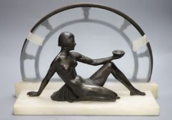 An Art Deco style bronze of nude reclining female figure on white marble plinth, length 42cm