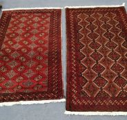 A near pair of Belouch burgundy ground rugs, larger 200 x 110cm