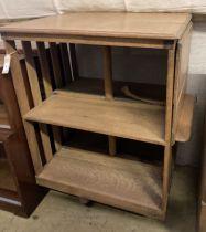 An Arts & Crafts light oak drop flap revolving bookcase, with a folding reading slope, width 68cm,