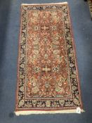 A Persian burgundy red ground rug, 146 x 69cm
