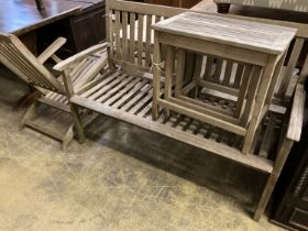 A weathered teak garden bench, length 129cm together with a teak steamer chair and nest of three