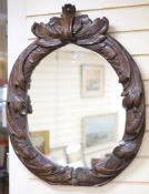 An early 19th century oval carved wall mirror