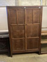 An Arts & Crafts style panelled oak two door wardrobe, width 105cm, depth 55cm, height 168cm