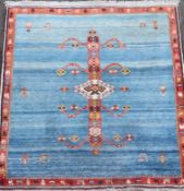 An Iranian Qushqa'i Gabbeh blue ground carpet, with central geometric motif and single row border,