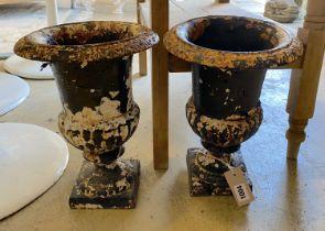 A pair of Victorian cast iron campana shaped garden urns, height 32cm
