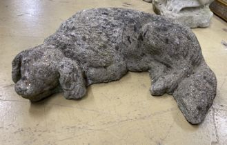 A reconstituted stone garden ornament of a sleeping spaniel, length 50cm