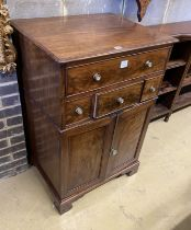 A Regency mahogany cupboard, fitted four drawers over a pair of fielded panelled doors (altered),
