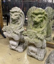 A pair of reconstituted stone lion and shield garden ornaments, height 56cm