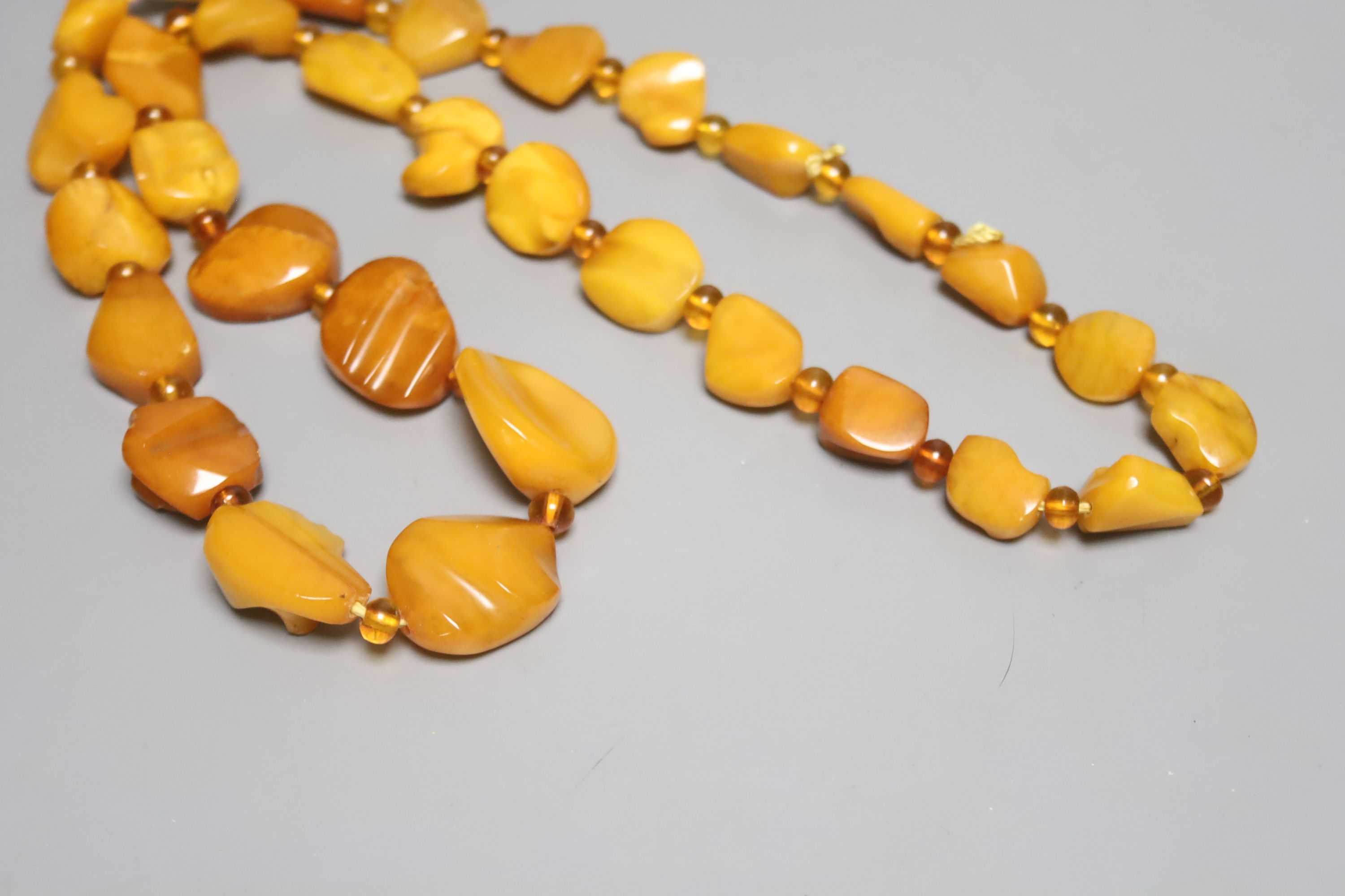 A single strand graduated amber pebble necklace, with amber bead spacers, 82cm, gross 84 grams.