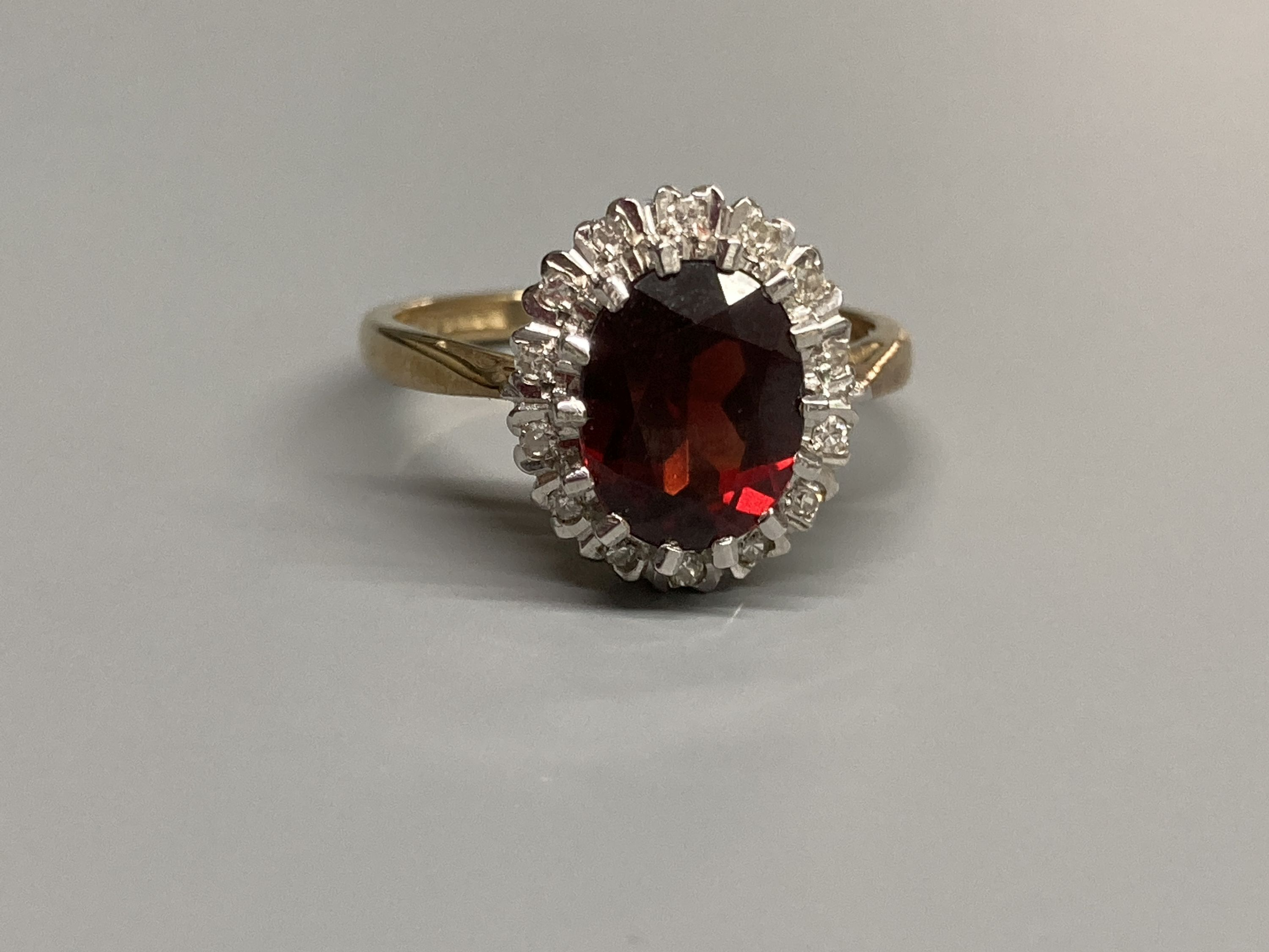 A modern 9ct gold, garnet and diamond set oval cluster ring, size N, gross 3.4 grams. - Image 2 of 3