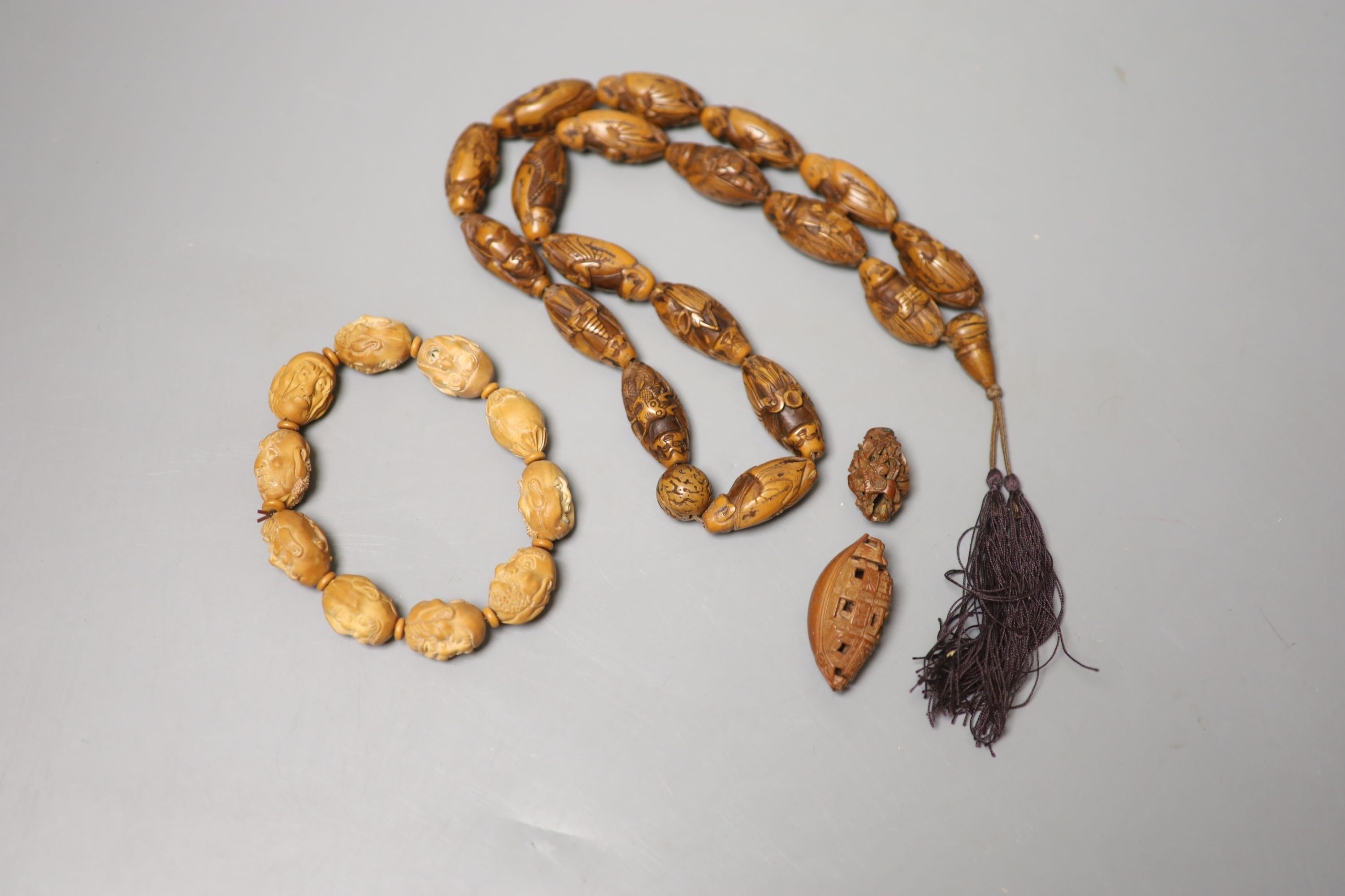 A coquilla nut necklace, bracelet and two small ornamental carvings