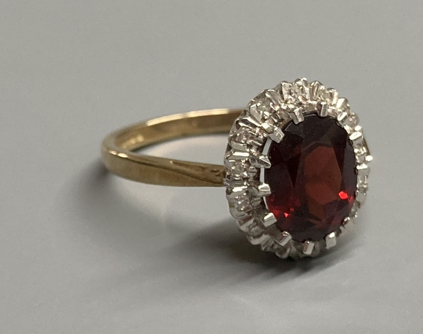 A modern 9ct gold, garnet and diamond set oval cluster ring, size N, gross 3.4 grams.