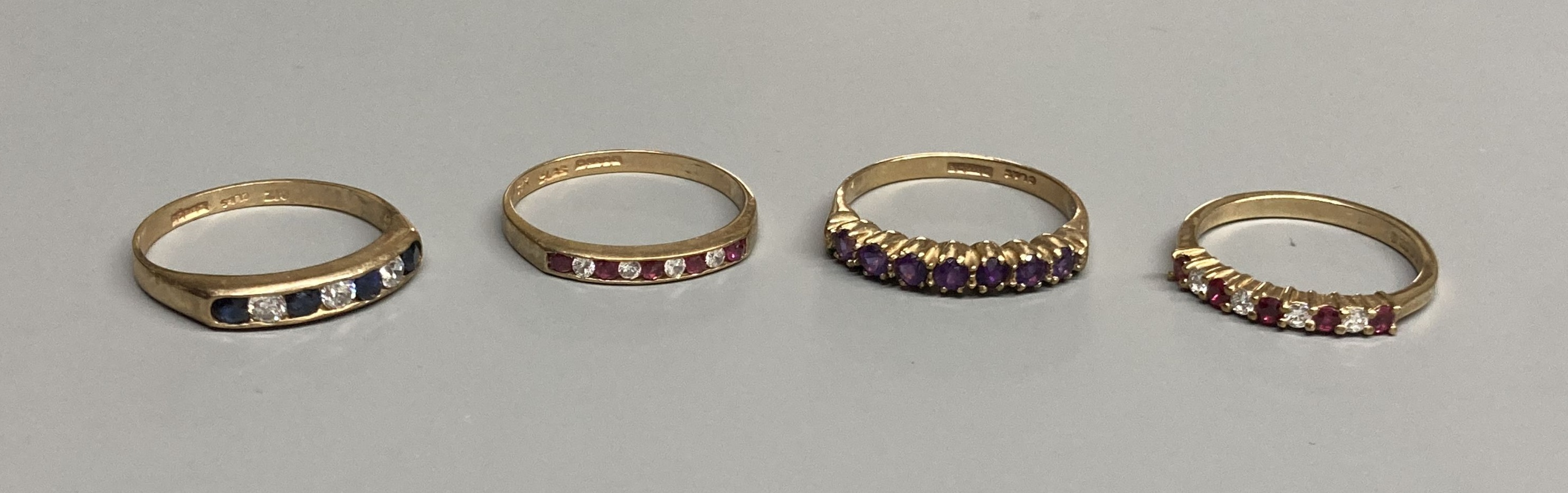 A modern 9ct gold, ruby and diamond set half hoop ring and a similar amethyst ring and two other 9ct