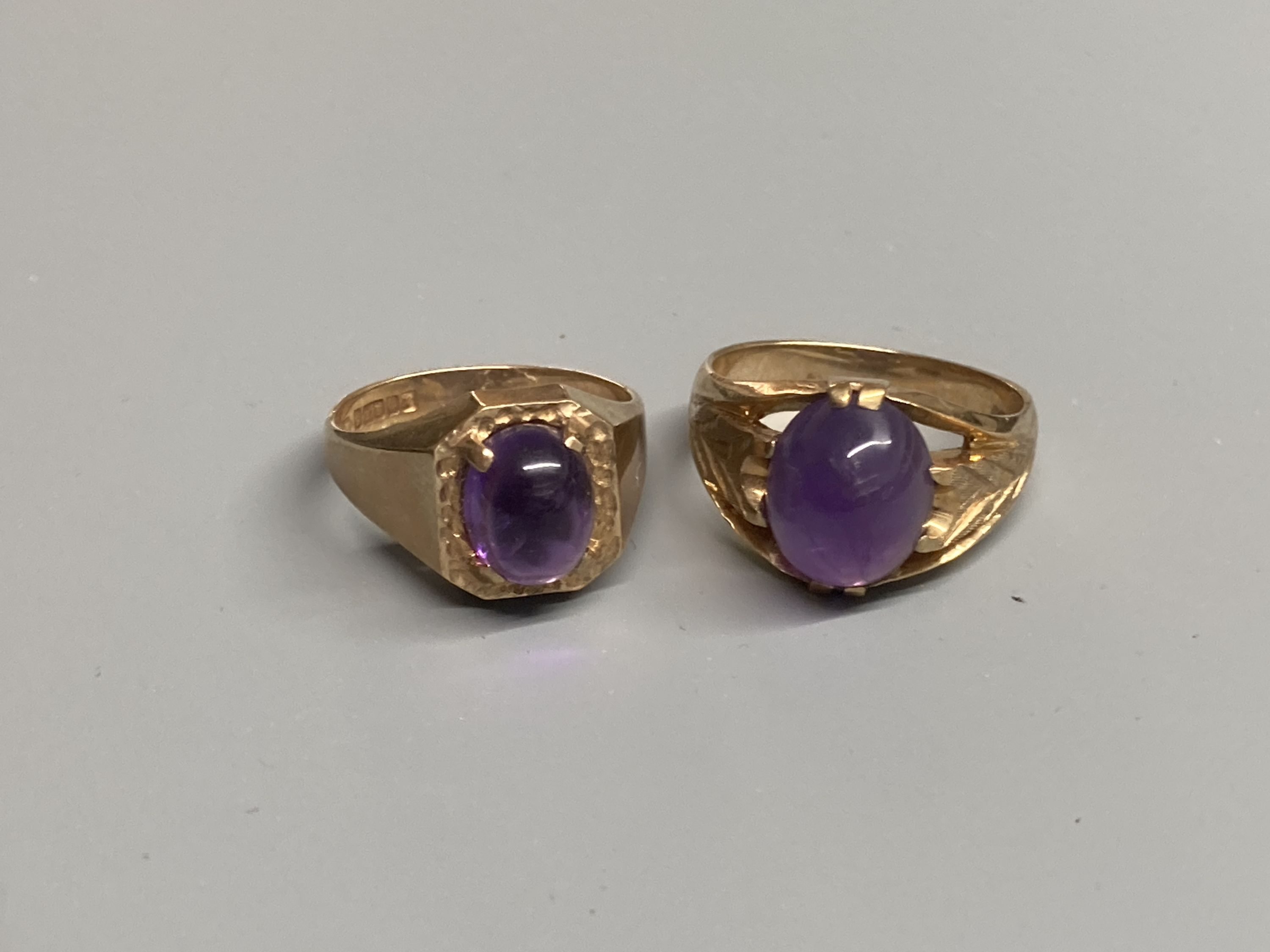Two modern 9ct gold and cabochon amethyst set dress rings, sizes Q/R & T,gross 11.6 grams.