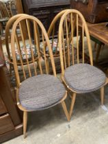 A set of four Ercol light beech comb back Windsor dining chairs