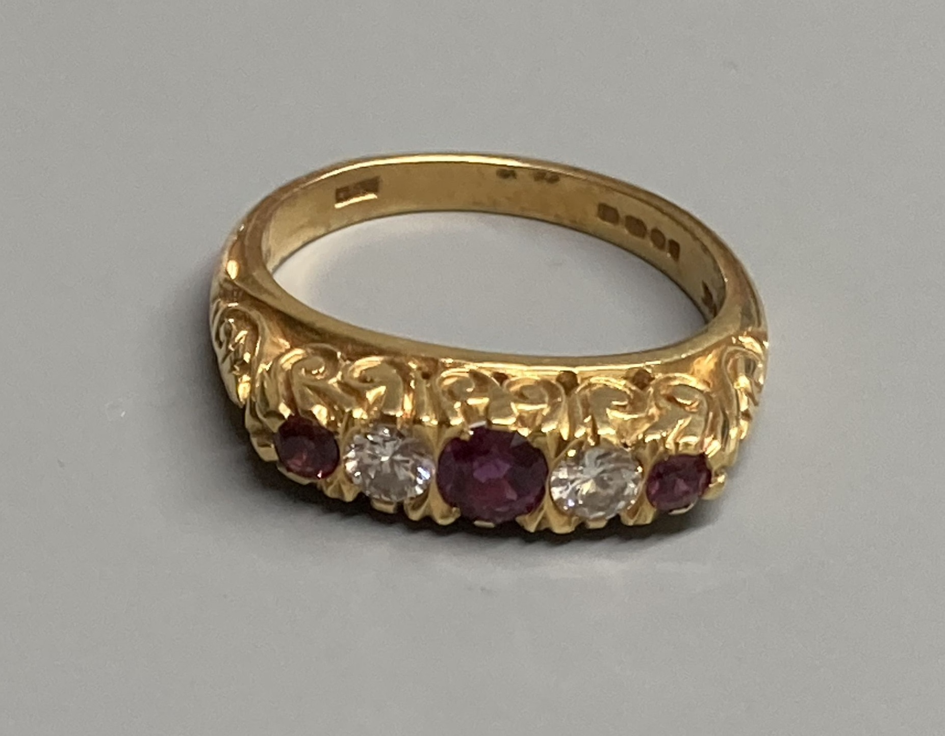A modern Victorian style 18ct gold, three stone ruby and two diamond set half hoop ring, size N,