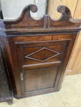 A George III oak hanging corner cabinet, width 72cm, depth 36cm, height 110cm
