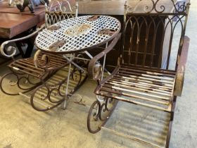 A pair of painted wrought iron garden rocking chairs together with a circular wrought iron folding