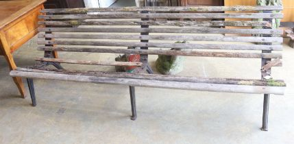 A slatted wood garden bench marked L M Furniture (in need of repair), length 244cm, depth 70cm,