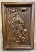 A rectangular carved oak wall panel depicting religious scene