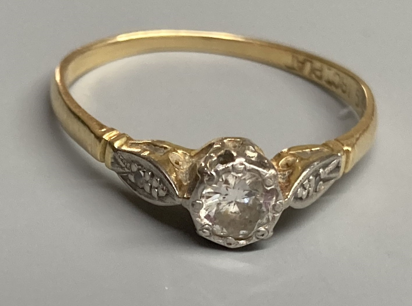 An 18ct & plat, single stone diamond ring, with diamond set shoulders, size P, gross 1.9 grams.